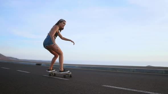 Cover Image for Girl Riding a Skateboard Near the Ocean and a Large Mountain in Slow Motion.