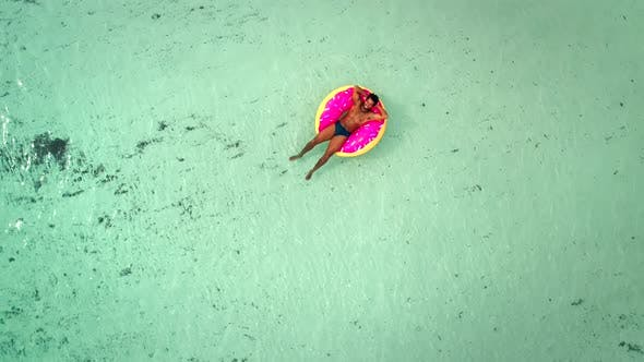 Thumbnail for Aerial view of man floating on inflatable donut mattress, relaxing.