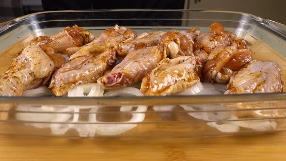 The marinated chicken wings are laid out on the onion rings in a glass baking dish.