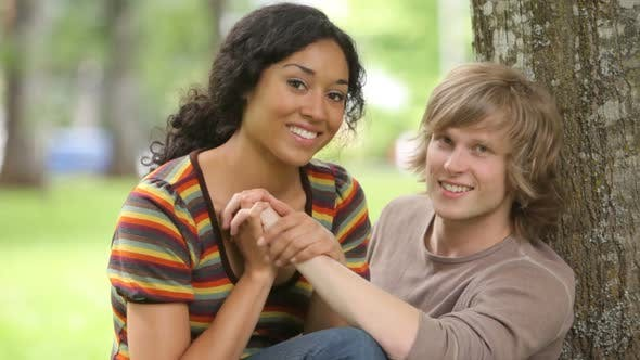 Portrait of couple sitting together by tree