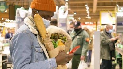 Black Man in Disposable Face Mask Walks Along Supermarket