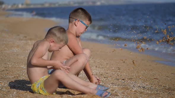Rest on the Sea with Children. The Boys Throw Up a Shell with Sand. Children's Emotions. Boys Throw