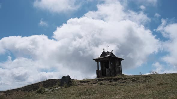 Thumbnail for Small Old Wooden Chapel on Top of Mountain on Background Moving Clouds in Sky.
