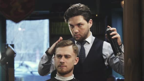 Thumbnail for Professional Barber Using Hairspray Styling Hair of a Young Man