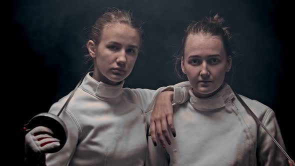 Thumbnail for Two Young Women Fencers Standing in the Dark Studio - Posing - Raising Their Heads Up and Looking in