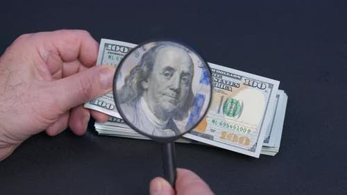 Person Checking Dollar Banknote for Authenticity with Magnifying Glassclose Up