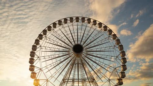 Ferris wheel silhouette - time lapse against orange clouds in the sky at sunset