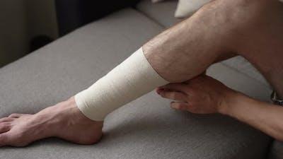 Man is Bandaging His Leg with an Elastic Bandage