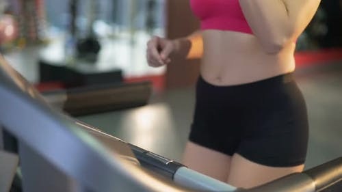 Healthy Fit Lady Exercising on Treadmill and Drinking Water for Refreshment