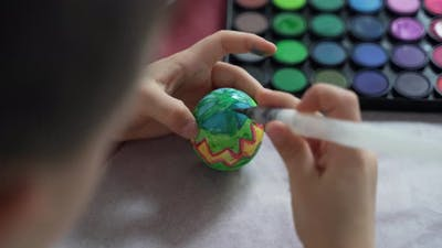 Close-up, a boy is painting an Easter egg