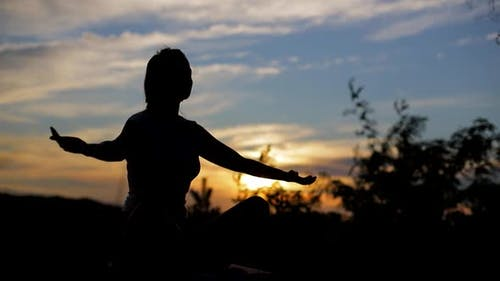 Silhouette of a Christian woman praying at sunset, outdoors