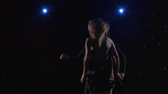 Flexible and Sensual Dancers Dance Ballroom Dancing in a Dark Studio in the Rain