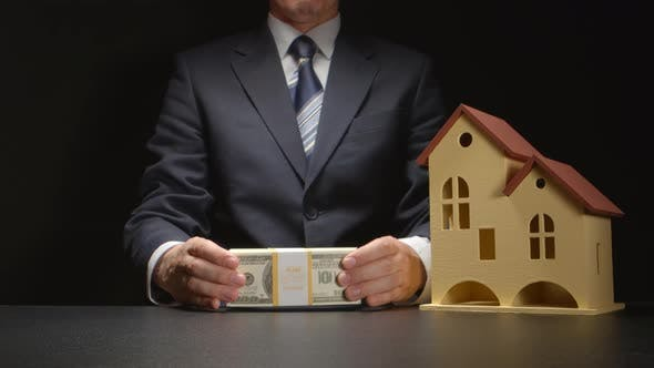 Businessman shows a money and gives it near a house model on a table