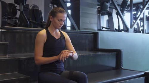A Fit Girl Turns on a Second Hand Watch for Sports Exercises on a Wristwatch