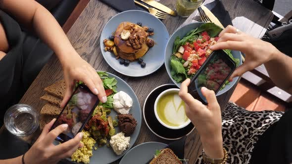 Thumbnail for Top View of Hands of Two People Taking Pictures of a Colorful Healthy Brunch