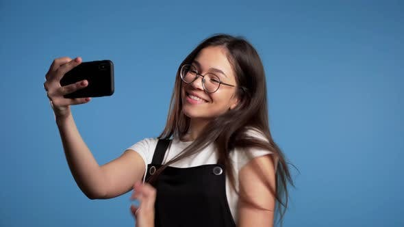 Thumbnail for Smiling Happy Asian Girl in Glasses Making Selfie on Smartphone Over Blue Background