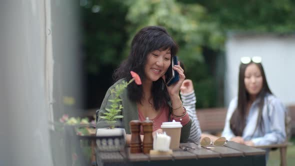 Thumbnail for Cheerful Asian Woman Sitting in Outdoor Restaurant and Chatting on Cell Phone