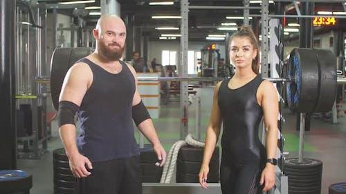 Fröhliche Happy Powerlifter in schwarzer Sportbekleidung stehen nach dem Wettkampf zusammen