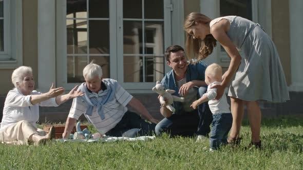 Thumbnail for Family Teaching Toddler to Walk