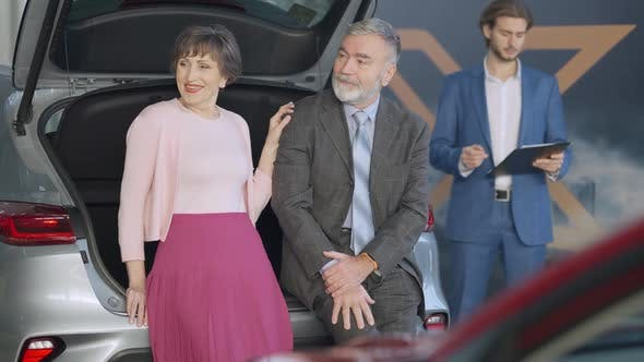 Smiling Senior Couple of Retirees Choosing New Automobile in Car Dealership with Dealer Standing at
