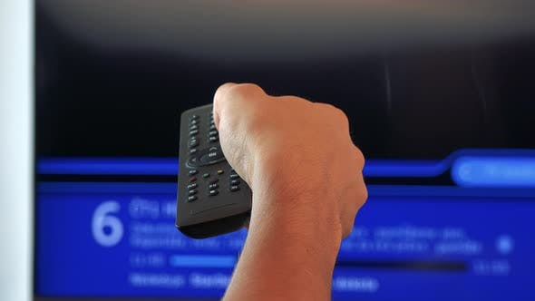 Thumbnail for A Hand with a Controller Switching Between Channels on a TV