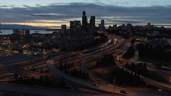 Cover Image for Night Aerial Of Seattle With Glowing Lights From Skyscrapers In City Skyline And Freeway Cars