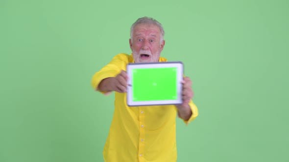 Cover Image for Happy Senior Bearded Businessman Showing Digital Tablet and Looking Surprised