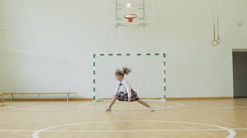 Little Girl Sits on the Twine in the School Gym. Girl Performs Gymnastic Twine in the Gym.