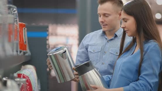 Thumbnail for A Man and Woman Hold in Their Hands an Electric Kettle in a Store Choosing Before Buying