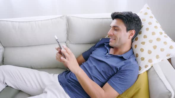 Man Lying on Couch Using Smartphone