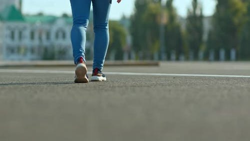 Woman Walks on the Asphalt Steps in Slippers