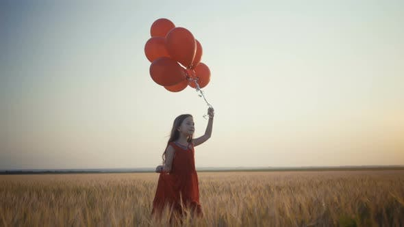Thumbnail for Happy Young Girl with Balloons Running in the Wheat Field at Sunset