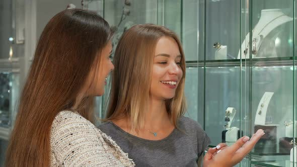 Cover Image for Two Female Friends Choosing Jewelry To Buy at the Store