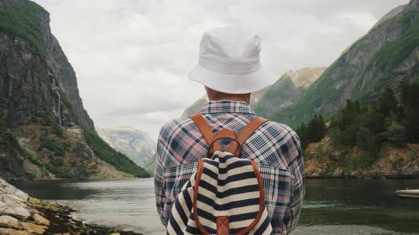 Thumbnail for A Tourist with a Backpack on His Back Admires the Picturesque Fjord in Norway. Active Lifestyle and