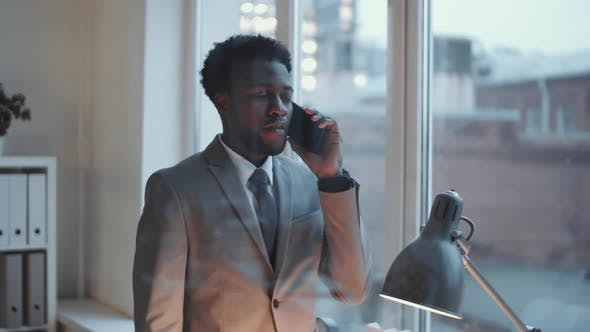 Thumbnail for Young Black Businessman Having Phone Conversation in Modern Office