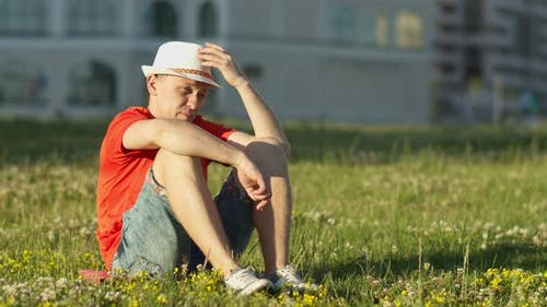 Guy in a white hat sits on the grass in a city park, camera movement
