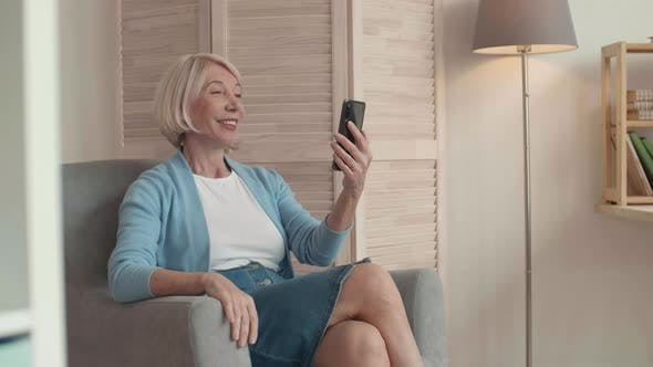 Woman Sitting in Arm-Chair with Phone