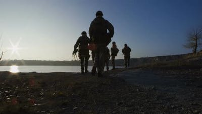 Equipped and Armed Soldiers Walking in Single File