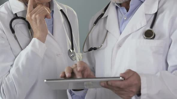 Cover Image for Doctors checking electronic medical records on tablet, working on diagnosis