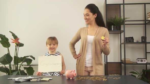Girl Smiles and Holds Cryptocurrency Sign Mother Holds Gold Bitcoin