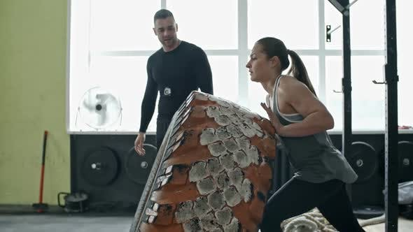 Cover Image for Woman Flipping Tire in Gym with Support of Coach