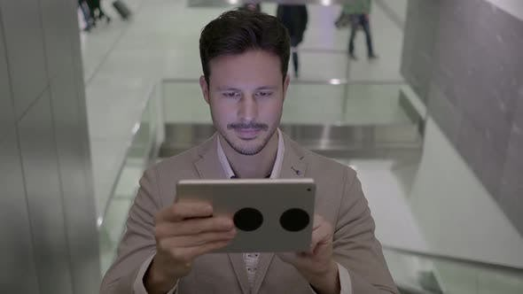 Thumbnail for Lifestyle Portrait of Attractive Young Male Entrepreneur Browsing the Web Tablet Screen