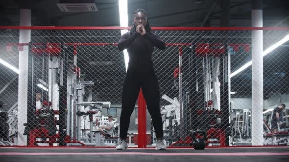 An Africanamerican Sportive Woman Squatting in a Gym
