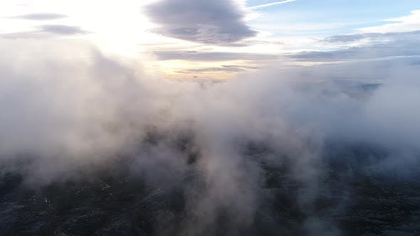 Surreal View Flying through Clouds at Sunset