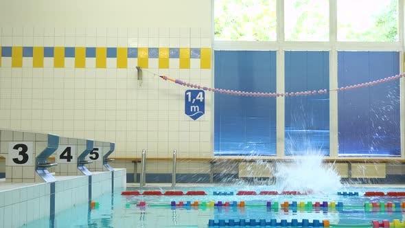 Thumbnail for Ein professioneller Schwimmer springt von einer Sprungplattform in ein Hallenbad