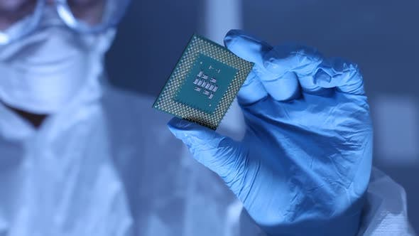 Cover Image for Man in clean room holds up computer cpu microchip