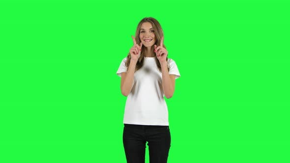Cover Image for Lovable Girl Smiling and Showing Heart with Fingers Then Blowing Kiss. Green Screen