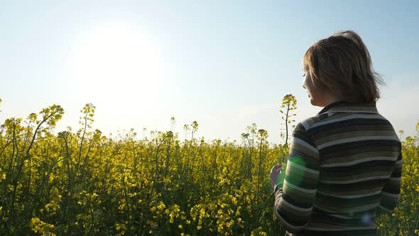 Thumbnail for Smiling Blonde Woman Standing in a Rapeseed Field at Splendid Sunset