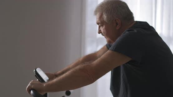Training auf stationärem Fahrrad für die Gesundheit des Herz-Kreislauf-Systems Der Mensch des mittleren Alters macht Übungen