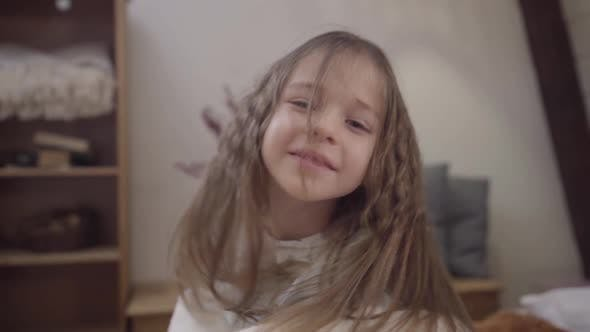 Thumbnail for Close-up Portrait of Cute Little Brunette Girl Shaking Long Hair. Smiling Happy Child Sitting on Bed
